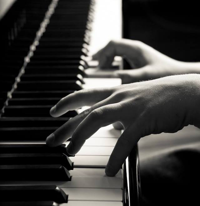black and white photo close up of someone playing piano