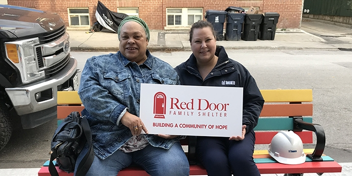 two people sitting on a bench holding a Red Door sign