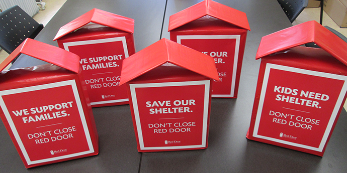 """little red cardboard houses with the text """"Save our Shelter"""""""