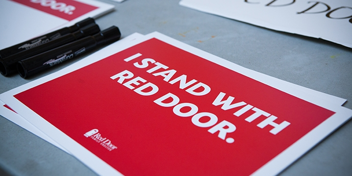"""A sign that reads """"I stand with a Red Door"""""""