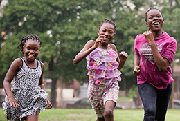 three smiling girls running toward the camera