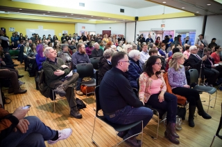 Large crowd seated at the community meeting