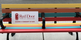 a colourful park bench with a Red Door sign on it