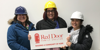 three people in hard hats holding a Red Door sign