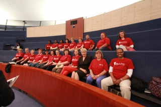 Rows of people wearing red door t-shirts at a council meeting