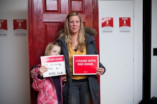 Mom and daughter stand in front of a Red Door holding signs of support for the Red Door