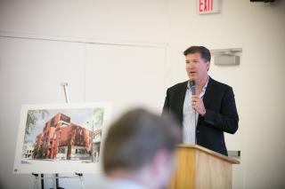 Chris Harhay talking at podium beside the shelter plan